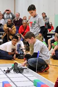 Brayden Spurlock (kneeling) and Griffin Minor (standing) turn on their robot.