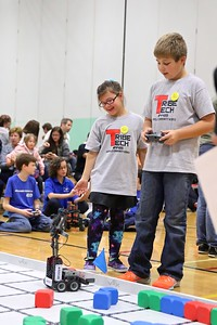 Alexis Tuttle and James Beck watch the robot move blocks past the flag.