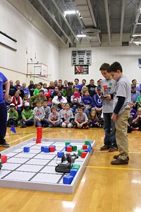 Brayden Spurlock (left) and Griffin Minor (right) maneuver their robot as Tribe Tech looks on.
