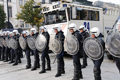 Belgian Police officers in full riot gear lining up in front of the water cannon, a brand new Ziegler WAWE 9.