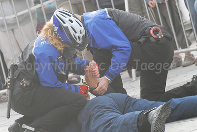 The arrest of a suspect by a police bike team during misty/foggy weather. The suspect is being handcuffed.