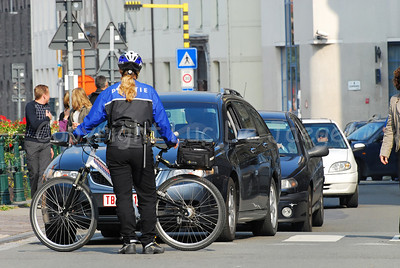 A police woman of the Maastricht bike team, the Netherlands, blocking the traffic on a crossing in the city of Ghent (Gent), Belgium.