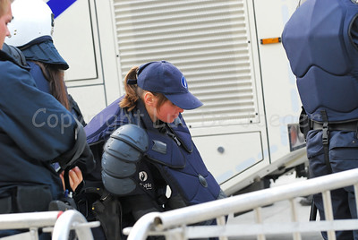 Belgian Police officers getting their riot gear on.