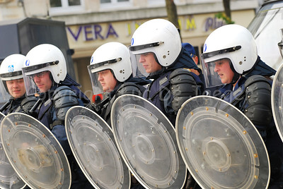 Belgian Police officers in riot gear lining up.
