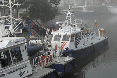 A patrol boat of the Belgian Federal Police in the mist/fog. In front is a boat of the Dutch Dutch National Police Services Agency (Korps Landelijke Politiediensten KLPD).