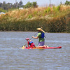 """A young girl gets a ride on a standup paddleboard on Sunday June 2nd, when Petaluma Small Craft Center, dedicated to securing permanent river access for all people-powered boaters, hosted Day on the River at the docks at Foundry Wharf and the North Bay Rowing Club. Members of the boating community gladly offered instruction and equipment free to everyone. This year, Aqus Community co-hosted, offering nourishment and entertainment (10am-4pm) while PSCC's volunteers concentrated on """"Putting Petaluma on the River"""" (10am-2pm). The event is a fundraiser for PSCC's planned dock-based rental center for the Turning Basin."""