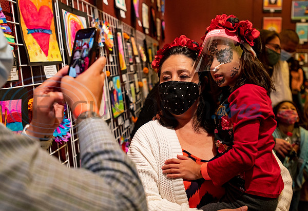 Richard Craft takes a photo of his wife Sophie and their daughter, Caldwell Arts Academy student Gabby, 6, who dressed up with flowers and skeleton face stickers the school's Day of the Dead celebration held inside Caldwell Auditorium on Monday, Nov. 2, 2020.