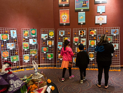 Caldwell Arts Academy families and students walk past walls of artwork during the school's Day of the Dead celebration held inside Caldwell Auditorium on Monday, Nov. 2, 2020.