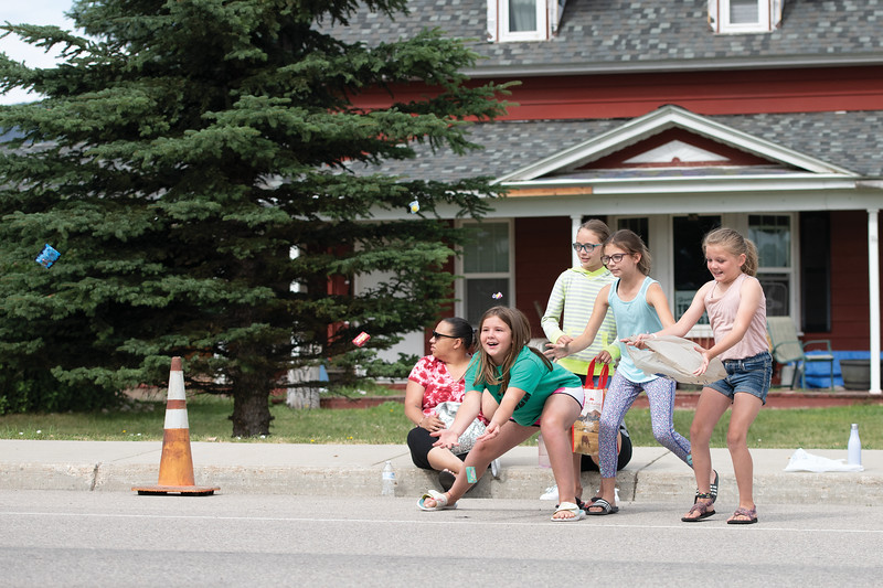 Matthew Gaston | The Sheridan Press<br>From left, Caelin Reish, Carlee Paxiao, Jamie McDonald and Megan Strainbrook rush to catch candy at the Dayton Days Parade Saturday, July 27, 2019.