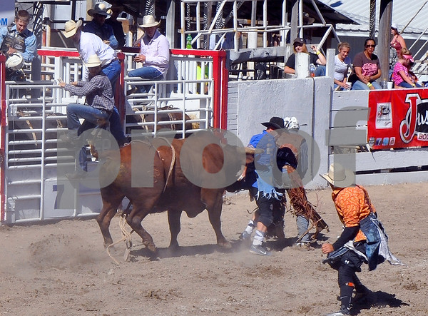 -Messenger photo by Joe Sutter<br /> <br /> Bullfighter Cory Wall gets a bit of a boot from a bull as he moves in to protect bull rider Nic Lica moments after he finished his ride. Bullfighter Will O'Connell moves in to help. Lica, of Garden City, won fourth place over the whole weekend with 79 points; the top bull riding score over the weekend was 88.