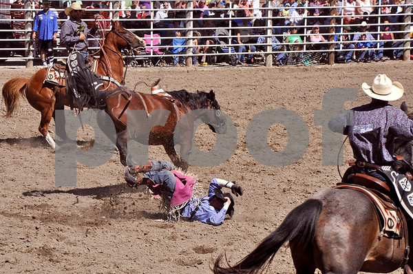 -Messenger photo by Joe Sutter<br /> <br /> Bee Jay Scott, of Otley, makes his landing after falling off during the bareback event at the Dayton Rodeo Monday. Two of the four highest scoring bareback rides were on Monday: Steven Peebles, Redmond Ore., 86 points, and Winn Ratliff, Leesville La., 84 points.