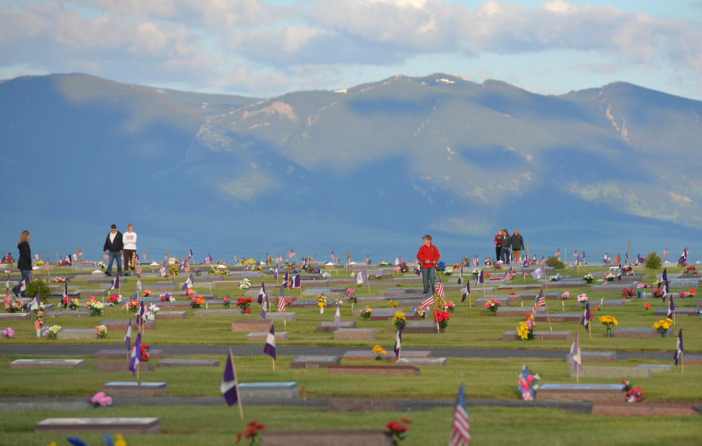 Justin Sheely | The Sheridan Press<br /> Community members walk in the Elks section with the Bighorn Mountains in view during morning decorating on Memorial Day at the Sheridan Municipal Cemetery. Members of the American Legion Post #7, Veterans of Foreign Wars, Disabled Veterans and community members decorated the headstones of veterans with flags.