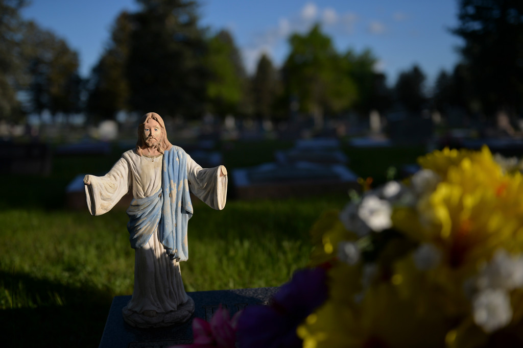 Justin Sheely | The Sheridan Press<br /> An image of Christ stands over a gravestone during morning decorating on Memorial Day at the Sheridan Municipal Cemetery. Members of the American Legion Post #7, Veterans of Foreign Wars, Disabled Veterans and community members decorated the headstones of veterans with flags.