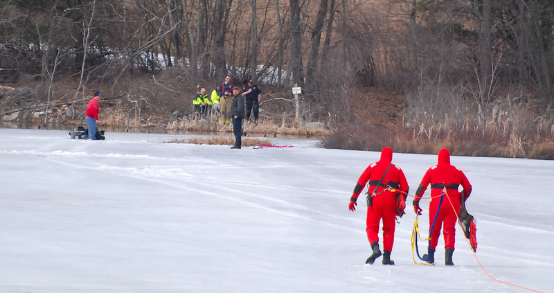 Rescure members walking toward person that went through ice and was stuck standing on his ATV