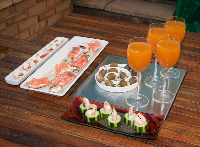 Canapes<br /> Smoked Salmon with cream cheese on melba toast, Lime and coriander infused prawns on cucumbers, Tomato, mozzarella and olive oil boats, Mini chilli jam and goats cheese tartlets,  Ricotta and feta stuffed olives, Blanched garlic cloves with herbs<br /> Bellini