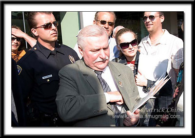 Lech Walesa getting his business cards out of his coat. Once he got them in hand, the crowd mobbed him to get the card (including me).