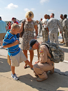 09-21-12  --dobbins homecoming 10--  Navigator Lt. Col. Greg Finkbiner of Kennesaw completes his first dad task by tying his son's shoe as he arrives home to his son Nicholas, 9, and his wife Tawnda.  STAFF/LAURA MOON.