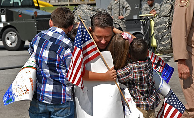 09-21-12  --dobbins homecoming 04--  Lt. Col. Chris Gohlke of Powder Springs receives a big hug from his children, from left, Andrew, 8, Austin, 8, Helena, 6, and Gavin, 4, as he arrives at Dobbins Air Reserve Base on Friday morning.  STAFF/LAURA MOON.
