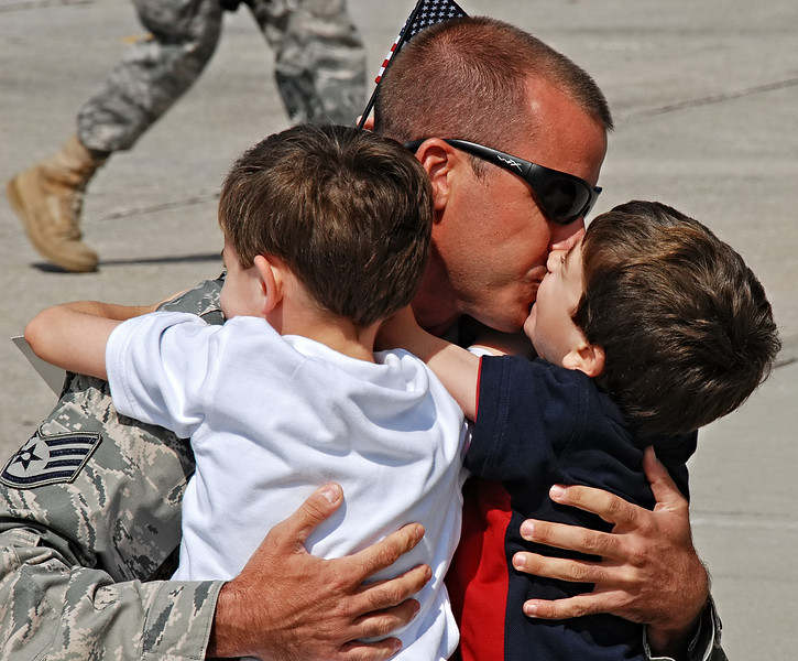 09-21-12  --dobbins homecoming 07--  Staff Sgt. Matthew Prater of Powder Springs gives his son Wes, 3, a kiss and hug as his other son Luke, 5, wraps his arms around his father.  STAFF/LAURA MOON.