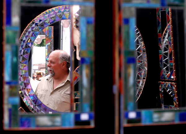 """Randy Romanin of Mountain Mosaics is reflected in one of his creations.<br /> The 32nd Annual  Downtown Boulder ArtFair continues Sunday fro 10 a.m. to 5 p.m. on the Pearl Street Mall.<br /> For more photos and a video of the fair, go to  <a href=""""http://www.dailycamera.com"""">http://www.dailycamera.com</a>.<br />  Cliff Grassmick / July 17, 2010"""