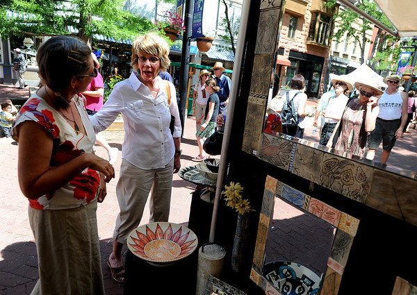 """Claire Pousson, left, of Bluehaven Porcelain, helps Pat Garcia at her booth on Saturday.<br /> The 32nd Annual  Downtown Boulder ArtFair continues Sunday fro 10 a.m. to 5 p.m. on the Pearl Street Mall.<br /> For more photos and a video of the fair, go to  <a href=""""http://www.dailycamera.com"""">http://www.dailycamera.com</a>.<br />  Cliff Grassmick / July 17, 2010"""