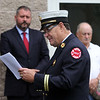 Dracut 9-11 ceremony at Jones Ave fire station. Dracut Fire Department chaplain Larry Zimmerman speaks. At rear are Dracut Board of Selectmen members Jesse Forcier, chair, and Joe DiRocco. (SUN/Julia Malakie)