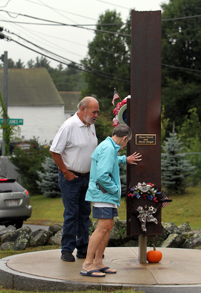 Dracut 9-11 ceremony at Jones Ave fire station. David Paquin, who designed the memorial, and his partner Catherine Kope, both of Dracut, walk around the memorial, which includes a beam from the World Trade Center. (SUN/Julia Malakie)