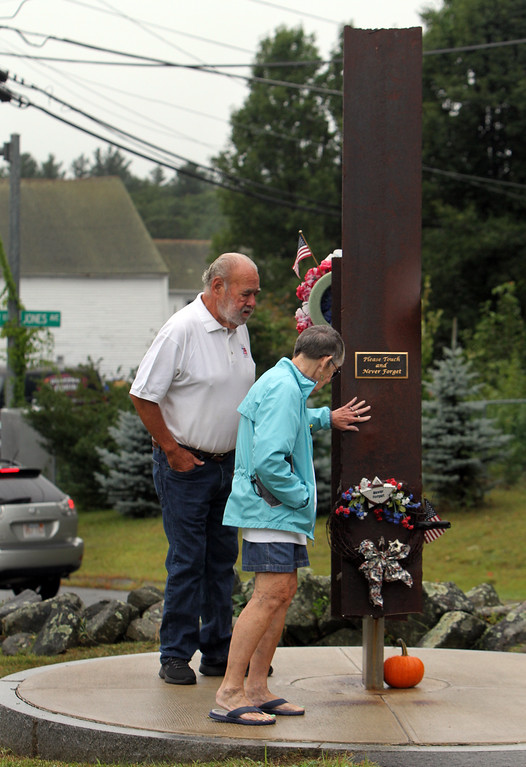 . Dracut 9-11 ceremony at Jones Ave fire station. David Paquin, who designed the memorial, and his partner Catherine Kope, both of Dracut, walk around the memorial, which includes a beam from the World Trade Center. (SUN/Julia Malakie)