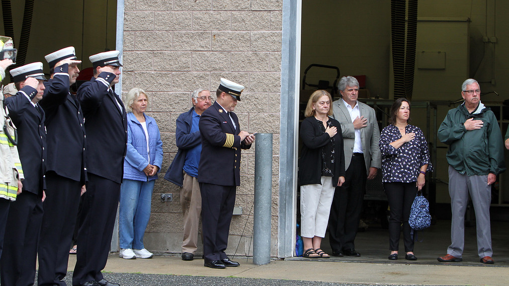 . Dracut 9-11 ceremony at Jones Ave fire station. Dracut Fire Department members, left, and at rear, from left John Ogonowski\'s sister Carol Ogonowski, and his uncle Al Ogonowski, Dracut fire chief Dave Brouillette, Ellie Richardson of Dracut, Dracut town manager Jim Duggan, School Board member Allison Volpe, and Tony Archinski. (SUN/Julia Malakie)