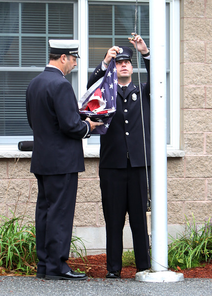 Dracut 9-11 ceremony at Jones Ave fire station. Dracut Fire Lt. Kevin Martin, left, and firefighter Mike Petrilli, raise the flag before lowering it to half-staff. (SUN/Julia Malakie)