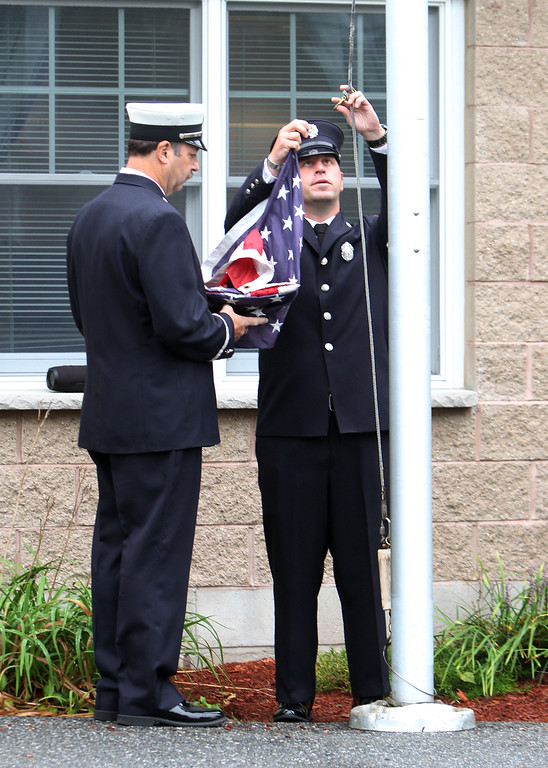 . Dracut 9-11 ceremony at Jones Ave fire station. Dracut Fire Lt. Kevin Martin, left, and firefighter Mike Petrilli, raise the flag before lowering it to half-staff. (SUN/Julia Malakie)