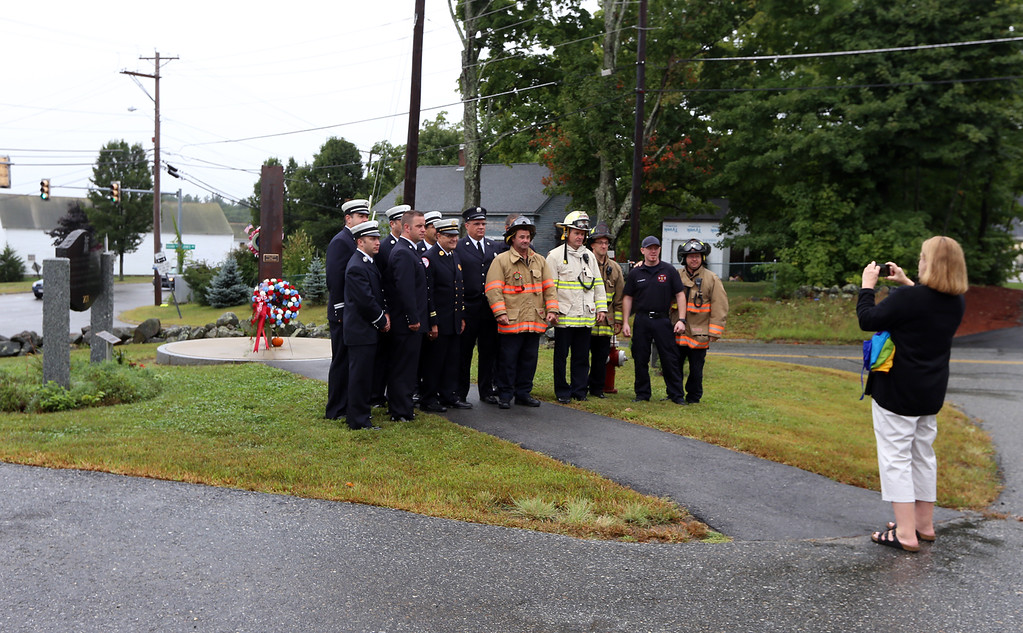 . Ellie Richardson of Dracut takes a picture of members of the Dracut Fire Department after the Dracut 9-11 ceremony at Jones Ave fire station. (SUN/Julia Malakie)