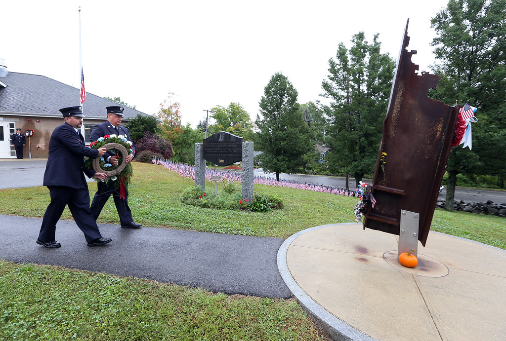 . Dracut firefighters Stephen Mullen, left, and Leo McMahon, carry wreath to the memorial during Dracut 9-11 ceremony at Jones Ave fire station. (SUN/Julia Malakie)