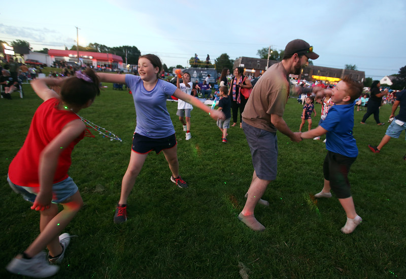 Annual concert and fireworks at Dracut school complex. Doug Marion of Nashua dances with his nieces and nephew, from left, Juliana Marion, 9, of Lowell, Carly Smith, 10, of Tyngsboro, and James Marion, 7, of Lowell. (SUN/Julia Malakie)