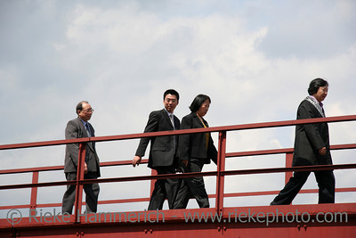 asian businessmen and businesswomen in a hurry - on a red bridge