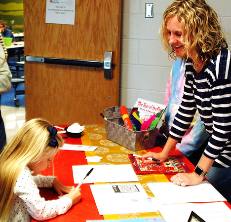 Debbie Blank | The Herald-Tribune<br /> Stacey Prewitt, one of many parent organizers, helps first-grader Madi Metcalf sign in at the the second Mandarin Dual Language Immersion Family and Community Night at Batesville Primary School April 25 at 6  p.m.