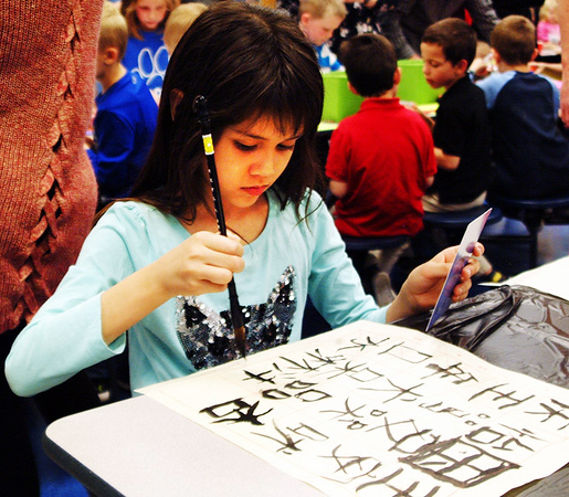 Debbie Blank | The Herald-Tribune<br /> Second-grader Elizabeth Washburn uses ink to practice her Chinese characters.