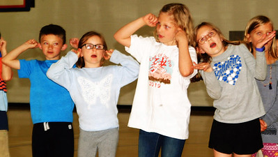 """Debbie Blank   The Herald-Tribune These four students were among about 40 who sang """"Two Little Tigers"""" in Chinese in the BPS gym before families visited different stations."""