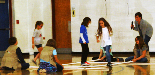 Debbie Blank | The Herald-Tribune<br /> Girl Scouts helped students play a bamboo jumping game in the gym.