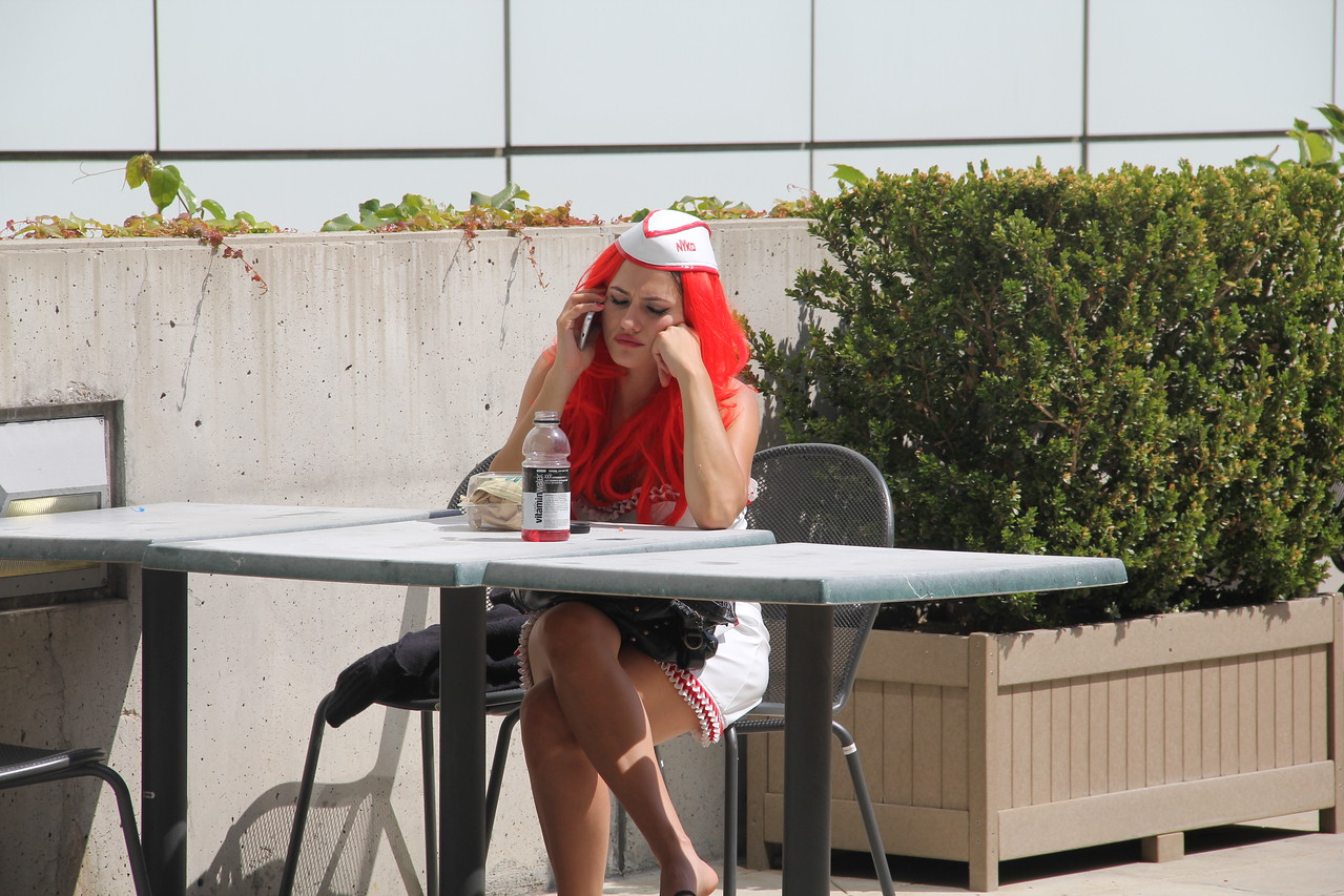 An E3 booth babe takes a lunch break, phones home to real world.