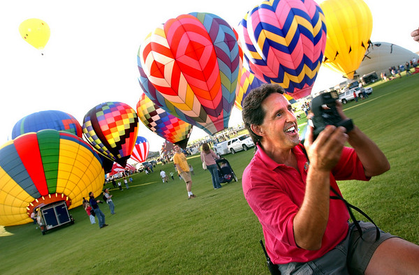 N0520BALLOON240.JPG<br /> <br /> Jeff Meeker of Fair Winds Hot Air Balloons of Boulder takes polaroid photographs of his passengers before taking them into the sky with around 60 other hot air balloons as part of the Erie Town Fair on Saturday May 19, 2007.  If you missed the launch you can see another launch starting at 6 am on Sunday on the grounds of the Vista Ridge Golf Club. <br /> Photo by Paul Aiken / The Camera / May 19, 2007