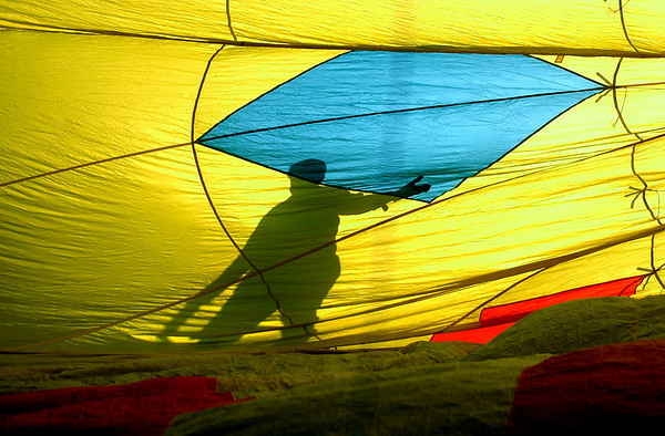 N0520BALLOON215.JPG<br /> <br /> A shadow created by the early morning sun shows a worker preparing on of the  60 hot air balloon that will rise into the sky as part of the Erie Town Fair on Saturday May 19, 2007 on the grounds of the Vista Ridge Golf Club.  If you missed the launch you can see another launch starting at 6 am on Sunday.<br /> Photo by Paul Aiken / The Camera / May 19, 2007