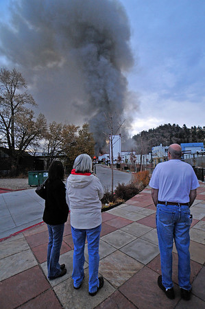 21EP View Anxious Moments.jpg Photo by Walt Hester<br /> Cheryl Grigsby of Rocky Mountain Memories, Susan Williams of Colorado Hats, and Tom DeLeo of DeLeo's Deli watch anxiously as flames and smoke rise above their businesses in the Park Theater Mall early Monday.