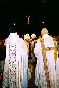 Priests and deacon file to the altar to say Mass on Sun.