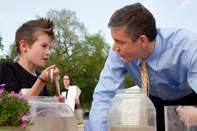 U.S. Sec. of Education Arne Duncan meets with Maya Willey of the No Child Left Inside Nature Club of Hillsmere Elementary School of Annapolis, MD. Maya shows him an eel. On the National Mall in Washington DC.  April 22, 2010 marked the 40th Anniversary of Earth Day. (Photo by Jeff Malet)
