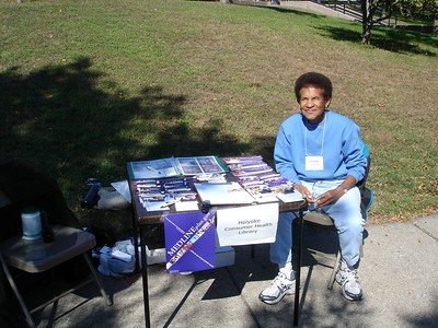 Doris McKethan sits at Holyoke Consumer Health Library, Inc. table with MedlinePlus promotional materials. [photo by Kathleen Packard]