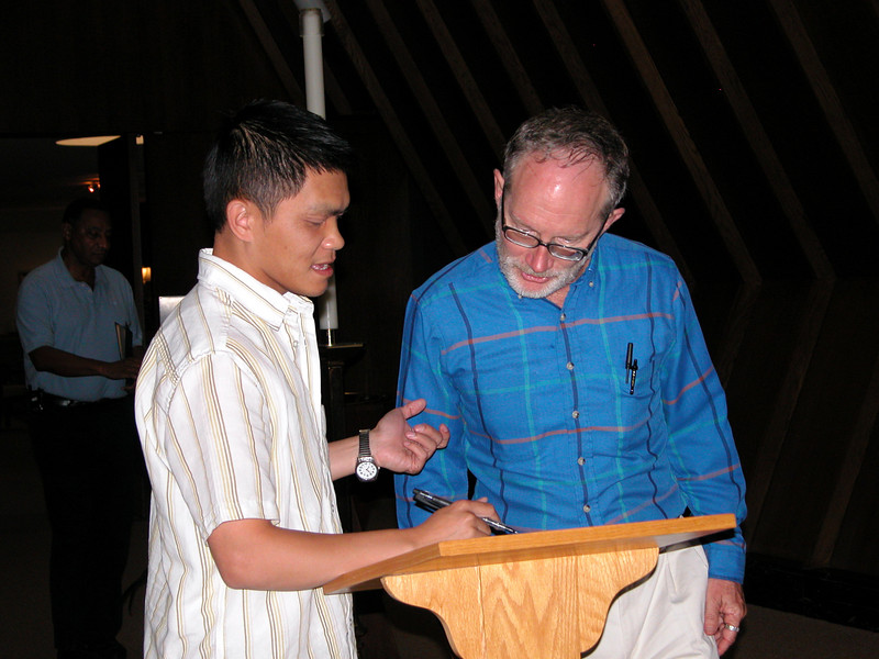 Fr. Tim Gray signs in with novice Long Nguyen.
