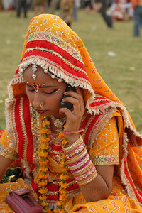 One of the performer busy on her mobile phone before the start of her show. Elephant Festival 2009 being celebrated in Jaipur on 10th Mach 2009. The elephant festival, Jaipur (Hindi: जयपुर),, is one of the most fascinating events organized in Rajasthan. This one day event coincides with Holi, the Indian festival of colors. The handlers or mahouts decorate their elephants in regal attire, and make them walk in procession at the start of the day. The procession heads to the Chaugan, the vast ground in Jaipur where this festival is hosted. The procession is watched by thousands of tourists and locals. Jaipur, Rajasthan, India.