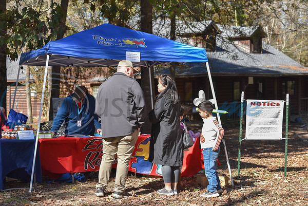 A family purchases tickets at Fall Festival hosted by Elijah's Retreat on Saturday. The event included auctions, bounce houses, bean bag toss, face painting, petting zoo and more. (Jessica T. Payne/Tyler Morning Telegraph)