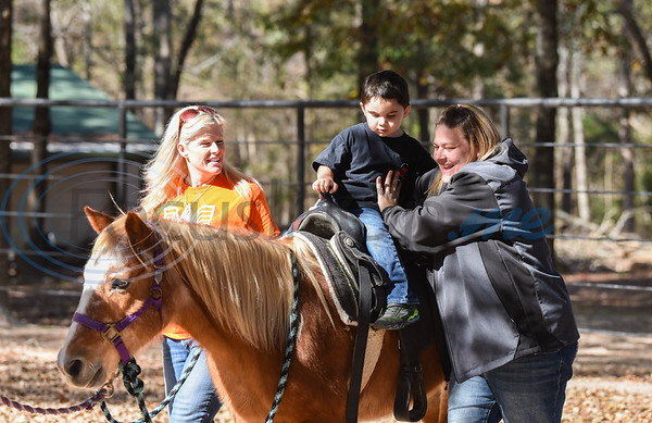 Dillon Castillo, 4, get a pony ride at the Elijah's Retreat Fall Festival in Jacksonville. The Saturday event included auctions, bounce houses, bean bag toss, face painting, petting zoo and more. (Jessica T. Payne/Tyler Morning Telegraph)